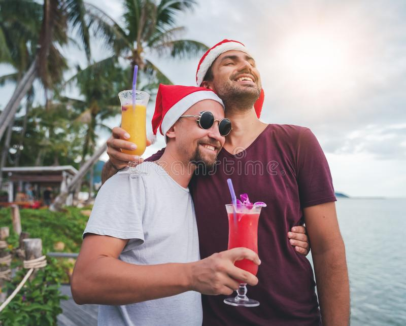 Happy handsome young men, gay family, celebrates New Year and Christmas at a tropical resort, LGBT values, equal rights for royalty free stock photos