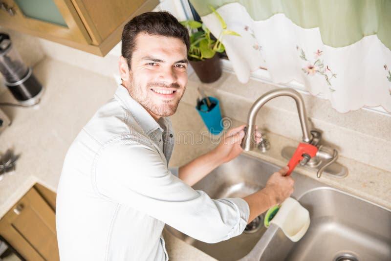 Happy handyman fixing a leaky faucet royalty free stock photo