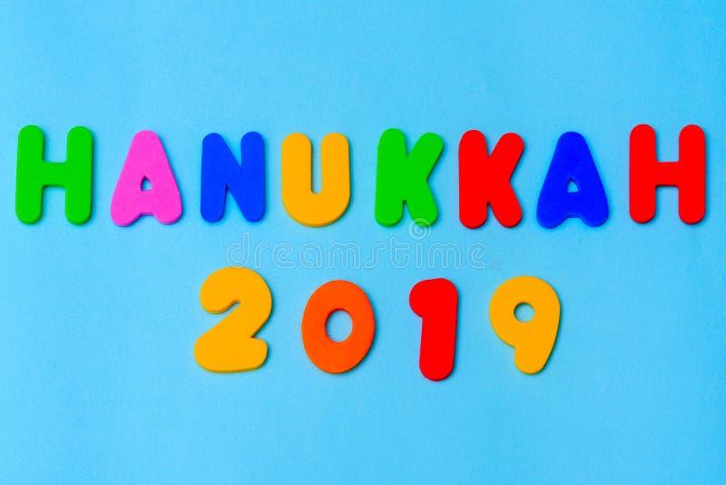 Happy Hanukkah 2019 colorful text on blue background.Jewish holiday Chanukah. stock photo