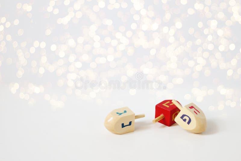 Happy Hanukkah greeting card, invitation Traditional Jewish Festival of lights holiday symbols. Wooden dreidel toys on stock photos