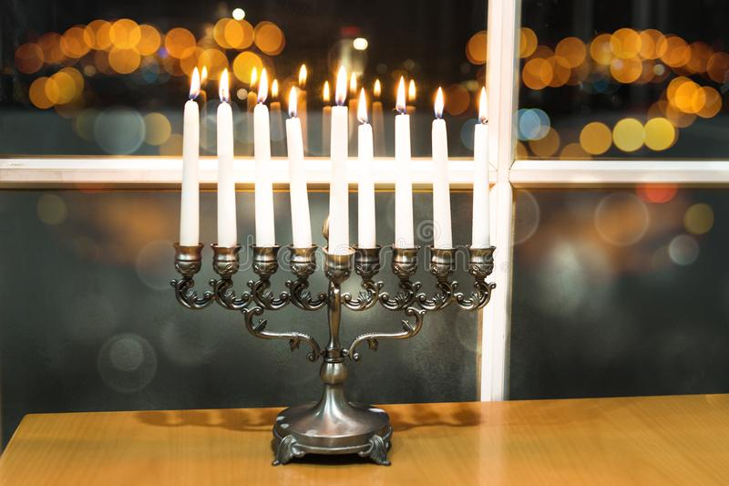 Happy Hanukkah. Low key image of jewish holiday Hanukkah with menorah by the window with the night view out of focus on Tel Aviv, royalty free stock images
