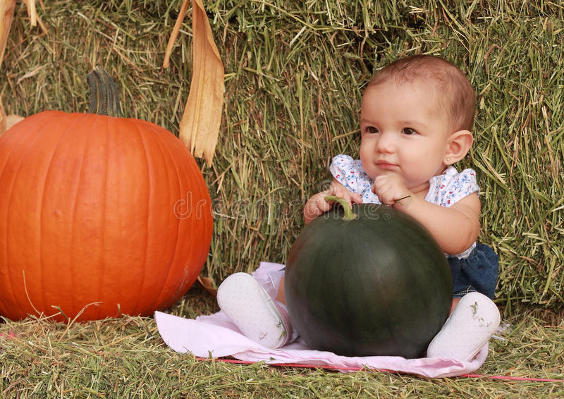 Happy Harvest Baby Girl. Autumn portrait of happy baby girl holding a sugar baby watermelon next to a pumpkin royalty free stock image