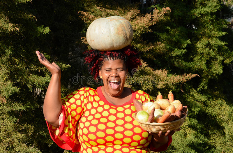 Happy harvest time. Outdoor portrait of a beautiful South African black woman with happy smiling facial expression carrying a crown pumpkin on her head and stock photo
