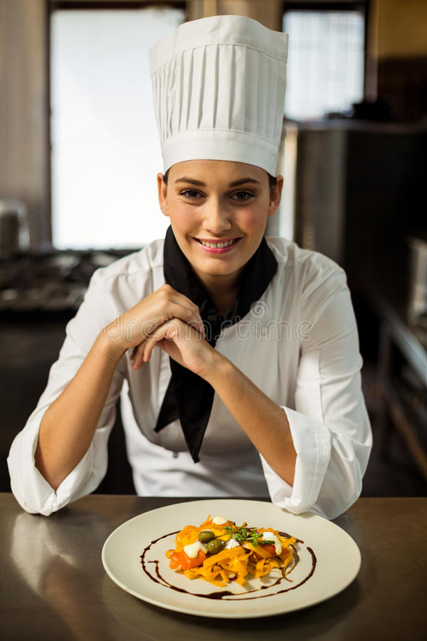 Happy head chef presenting her food stock images