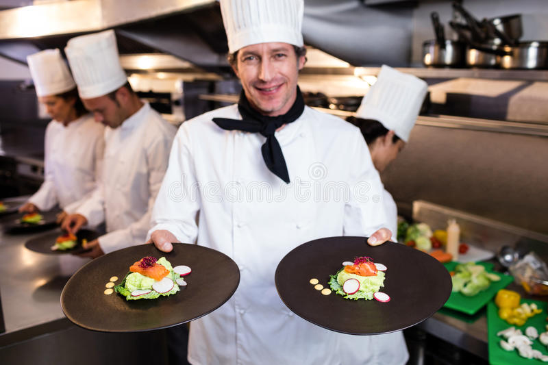 Happy head chef presenting his food plates. In the commercial kitchen while team working behind him royalty free stock photography