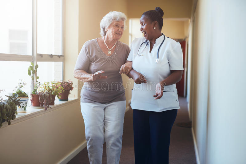 Happy healthcare worker walking and talking with senior woman stock images