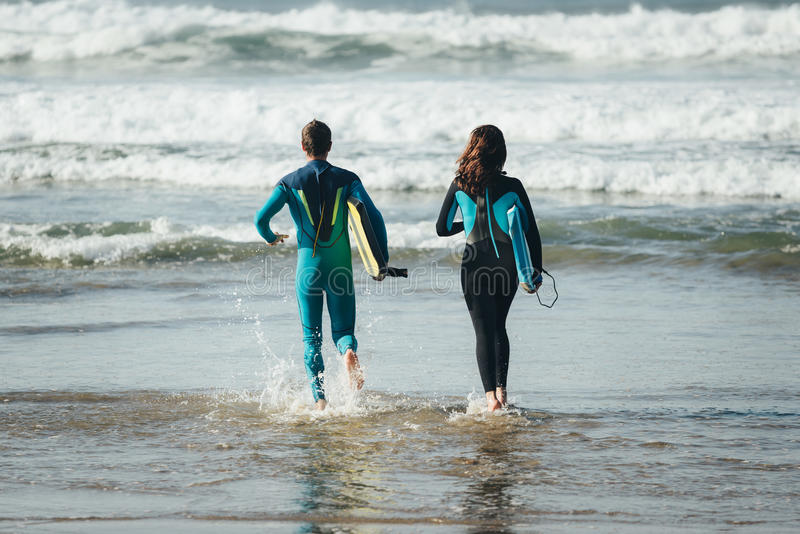 Happy healthy bodyboard surfing couple royalty free stock images
