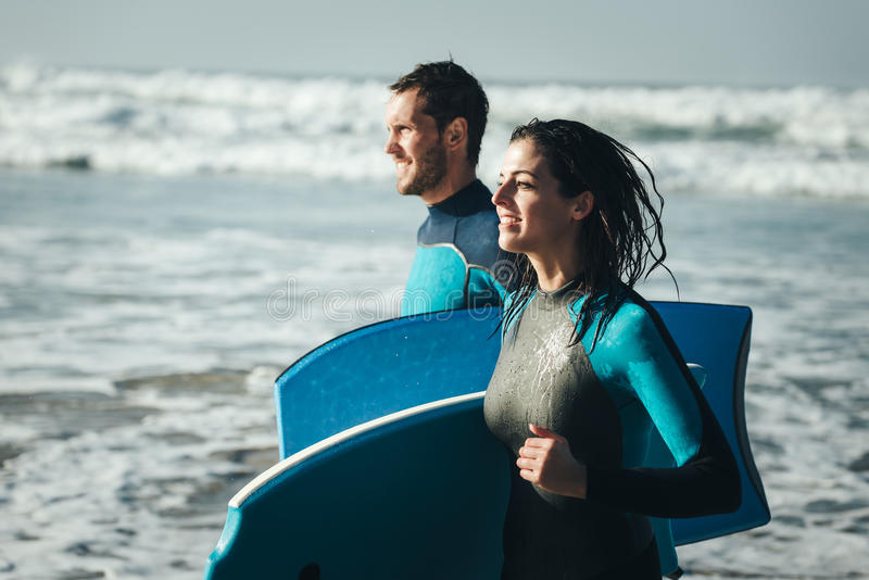Happy healthy bodyboard surfing couple stock photography