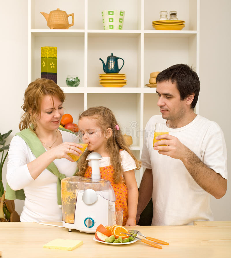 Happy healthy family drinking orange juice stock photo