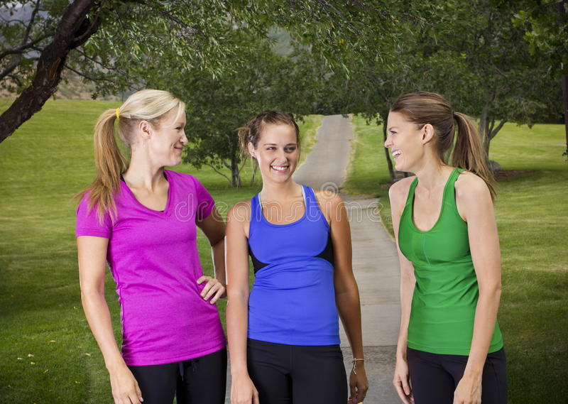Happy Healthy Fitness Women. Three healthy beautiful women laughing together before their workout outdoors royalty free stock image