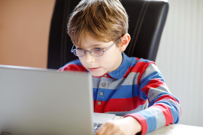 Happy healthy kid boy with glasses making school homework at home with notebook. Interested child writing essay with. Helping of internet. concetrated stock photos