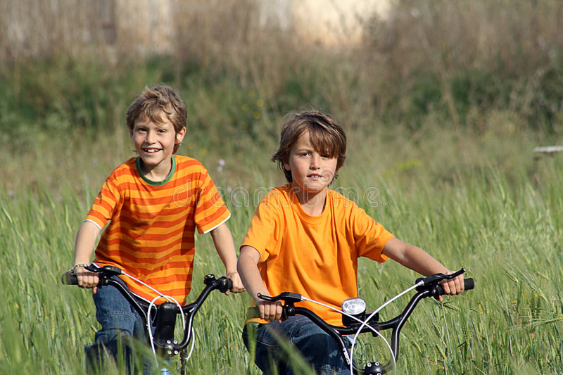 Download Happy Healthy Kids Riding Bikes Stock Photo - Image of meadow, outdoors: 733894