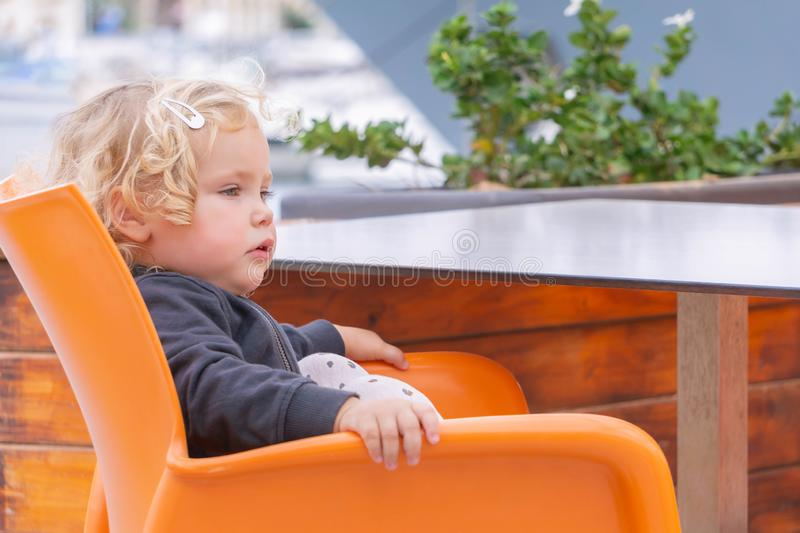 Blonde little girl sitting on orange chair in cafe outside and waiting for food royalty free stock photos