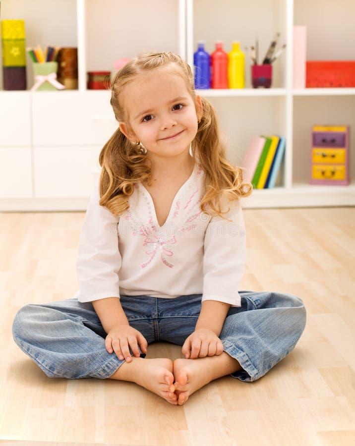 Happy healthy little girl sitting on the floor stock photos