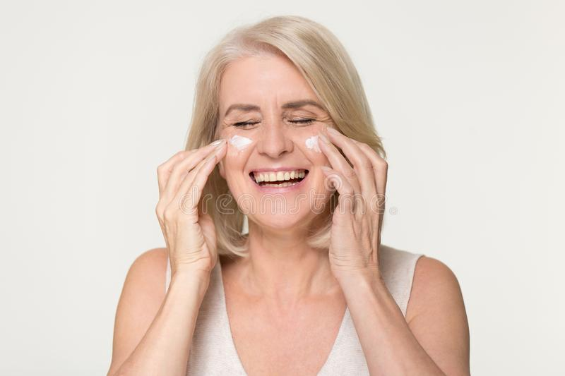 Happy old woman apply anti aging cream isolated on background stock photography