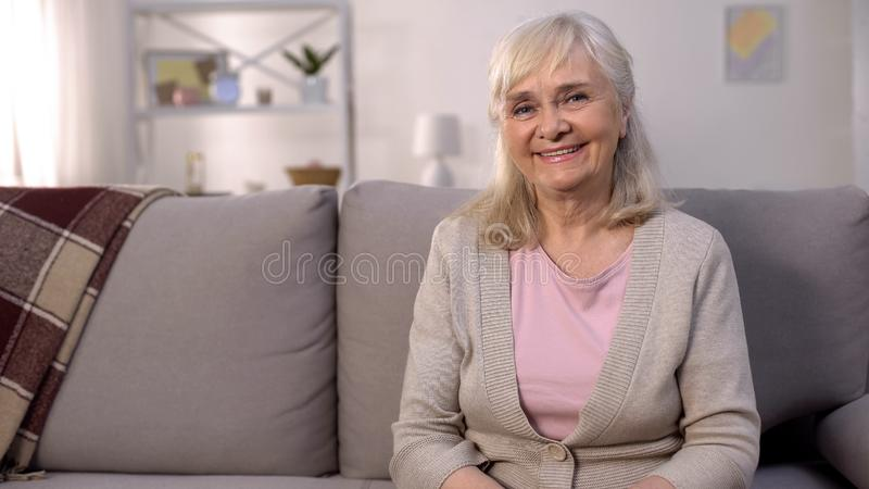 Happy healthy old woman smiling camera sitting sofa, retirement wellness, beauty stock images