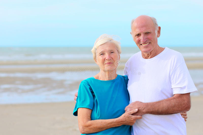 Happy healthy retired elders couple enjoying vacation on the beach royalty free stock images
