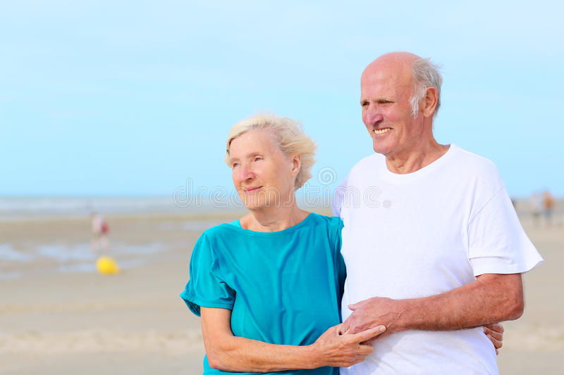 Happy healthy retired elders couple enjoying vacation on the beach. Loving amusing elderly couple enjoying the beach and sea breeze on sunny day - active healthy stock images