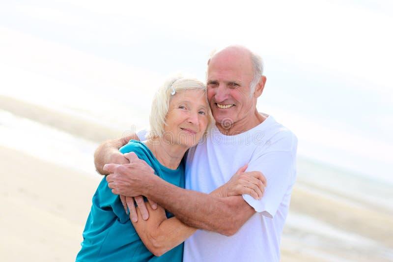Happy healthy retired elders couple enjoying vacation on the beach. Loving amusing elderly couple enjoying the beach and sea breeze on sunny day - active healthy royalty free stock photo