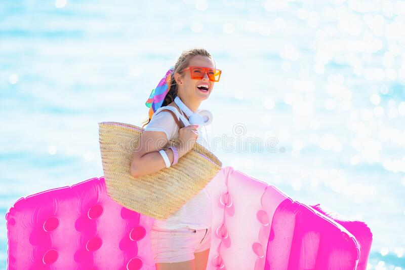 Happy healthy woman on seacoast holding inflatable mattress royalty free stock images