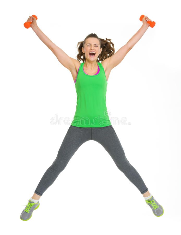 Happy healthy young woman with dumbbells jumping stock photography