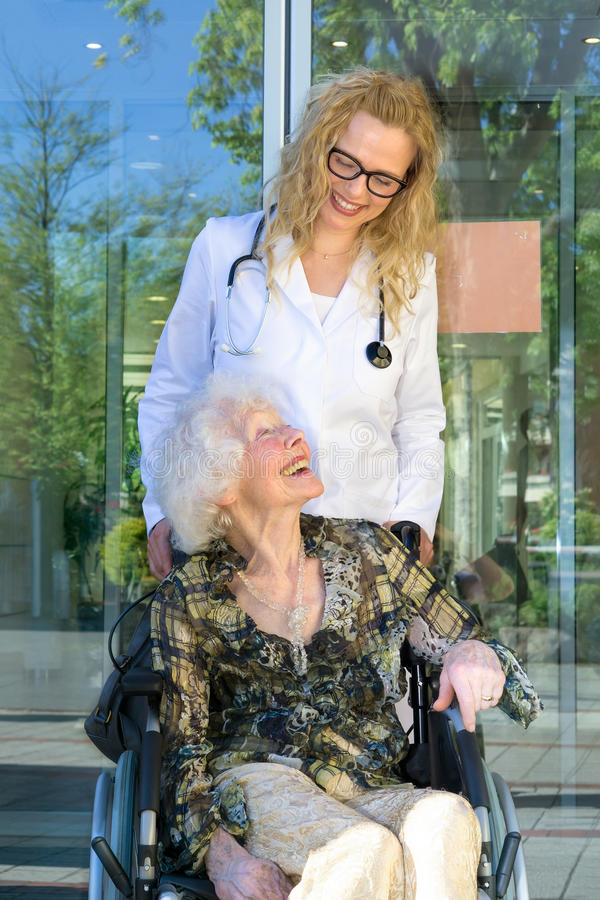 Happy Heath Care Assistant and Elderly Patient stock image