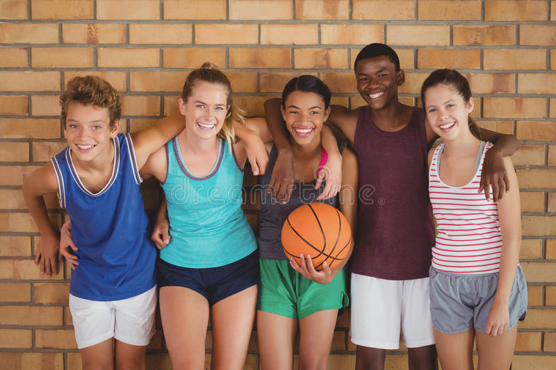Happy high school kids with arms around leaning against the wall in basketball court royalty free stock image