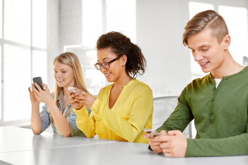 Happy high school students with smartphones stock image