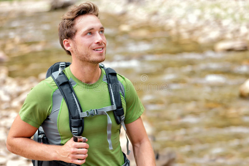 Happy hiker hiking in nature in clean river water. Aspiration young Caucasian man walking in summer nature environment with backpack. Hope, adventure travel or royalty free stock photo