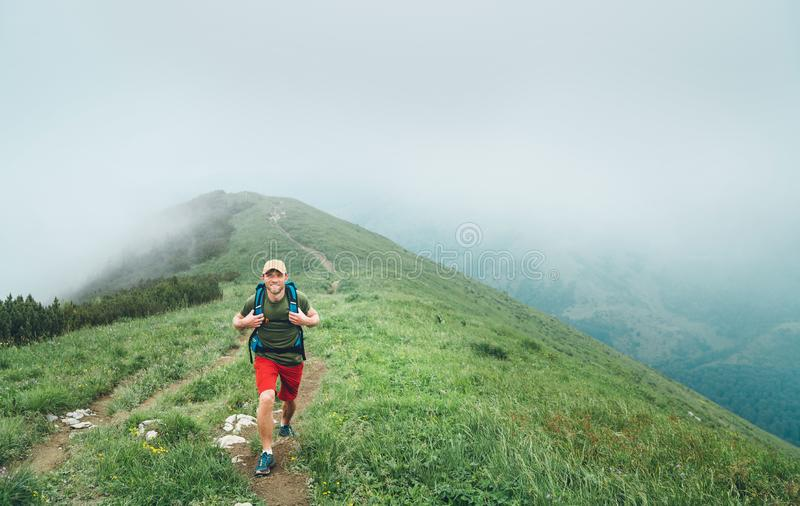 Happy hiker man walking by the cloudy and foggy weather mountain range path with backpack. Active sport backpacking healthy stock images