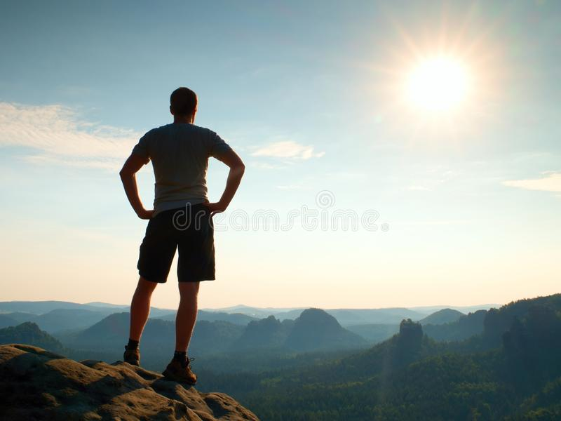 Happy hiker is standing on sharp cliff in rock empires park and watching over the misty and foggy morning valley to Sun. stock photography