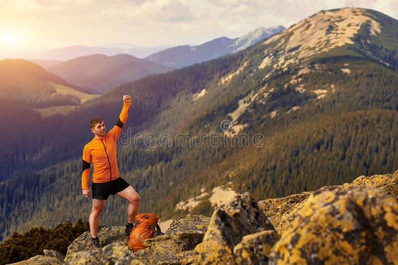 Happy hiker winning reaching life goal, success, freedom and happiness, achievement in mountains. Traveler with backpack stands on the top of mountain royalty free stock photography