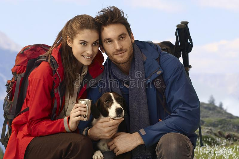 Happy hikers with dog. Enjoying spring in mountains stock photos