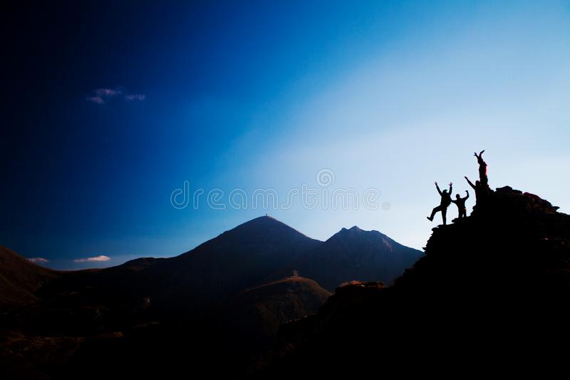 Happy hikers on a rock, silhouette. Silhouette group of happy hikers on a rock royalty free stock photography