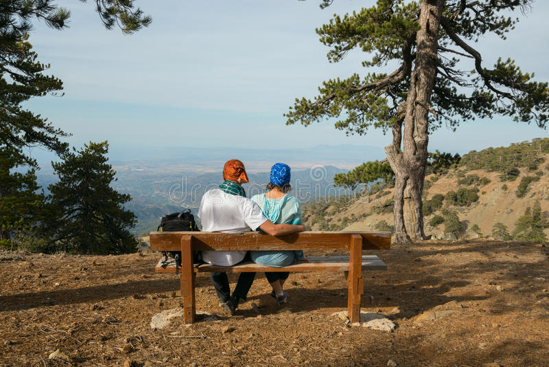 Happy hiking couple on a bench. Happy hiking couple sitting on a bench on edge of cliff and looking into the distance. Back view. Spring on Cyprus royalty free stock photography