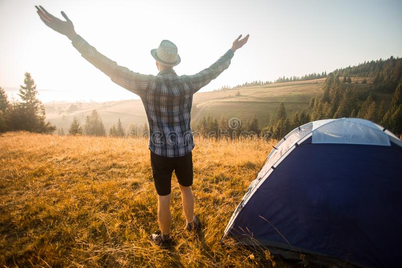 Happy hiking travel on top of mountain hand up looking to sunrise. Camp travel concept royalty free stock images