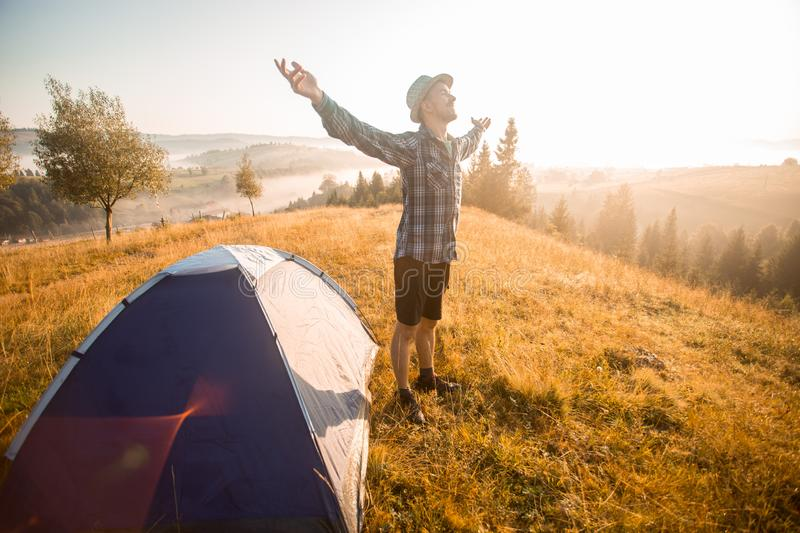 Happy hiking travel on top of mountain hand up looking to sunrise. Camp travel concept stock photos