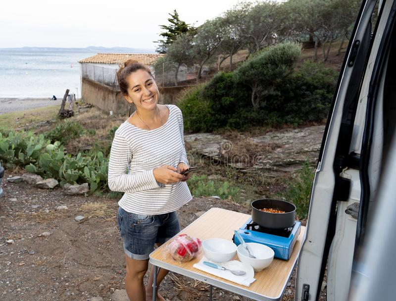 Happy hippie attractive young woman cooking outside her campervan near the beach stock photo