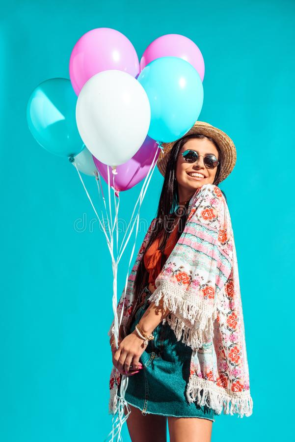 Happy Hippie girl holding colored helium balloons. Isolated on turquoise royalty free stock photography