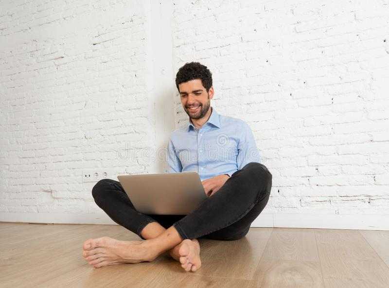Happy hipster blogger on laptop working on blog messaging fans and followers at new home royalty free stock photography
