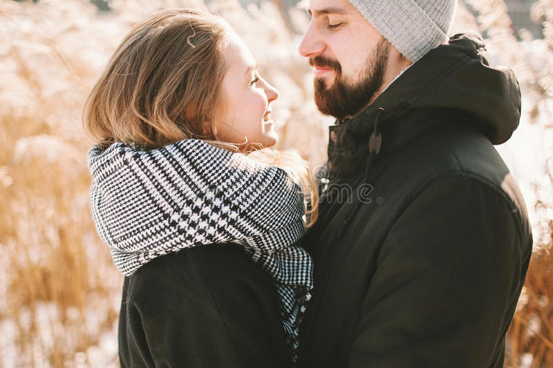 Happy hipster couple hugging near winter lake and reeds stock photography
