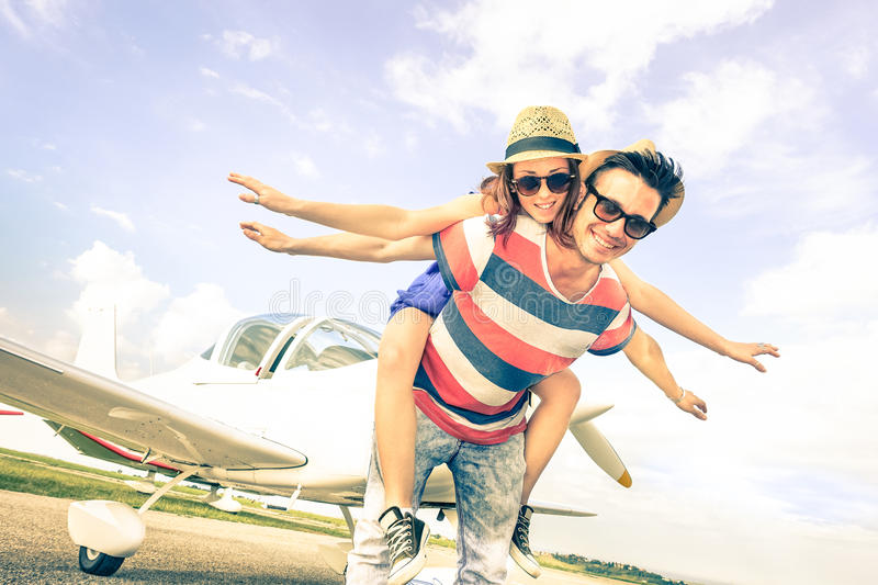 Happy hipster couple in love on airplane travel honeymoon trip royalty free stock image