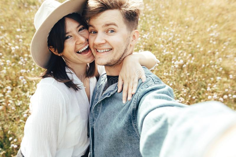 Happy hipster couple making selfie and smiling in sunny mountains. Stylish young family taking photo in travel and enjoying hiking stock images