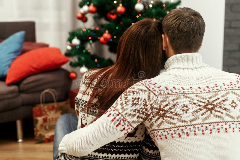Happy hipster family gently hugging looking at decorated christmas tree. joyful cozy moments in winter holidays. seasonal. Greetings. view from back. space for royalty free stock photography
