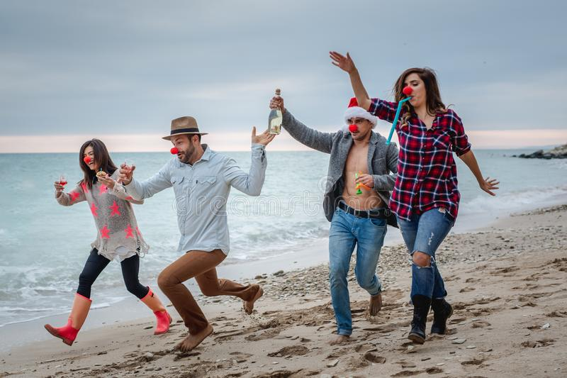Happy hipster friends running along the beach and celebrating New Year`s Eve. Happy people running along the beach celebrating New Year`s Eve. Dressed in bushy stock image