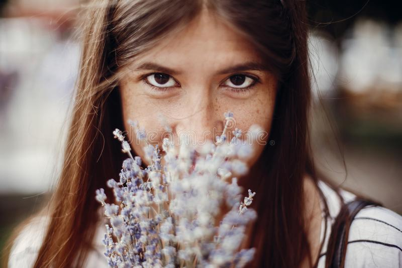 Happy hipster girl enjoying aroma of lavender bouquet. Calm atmospheric moment. Beautiful stylish young woman holding amazing lav. Ender flowers and smelling stock photo