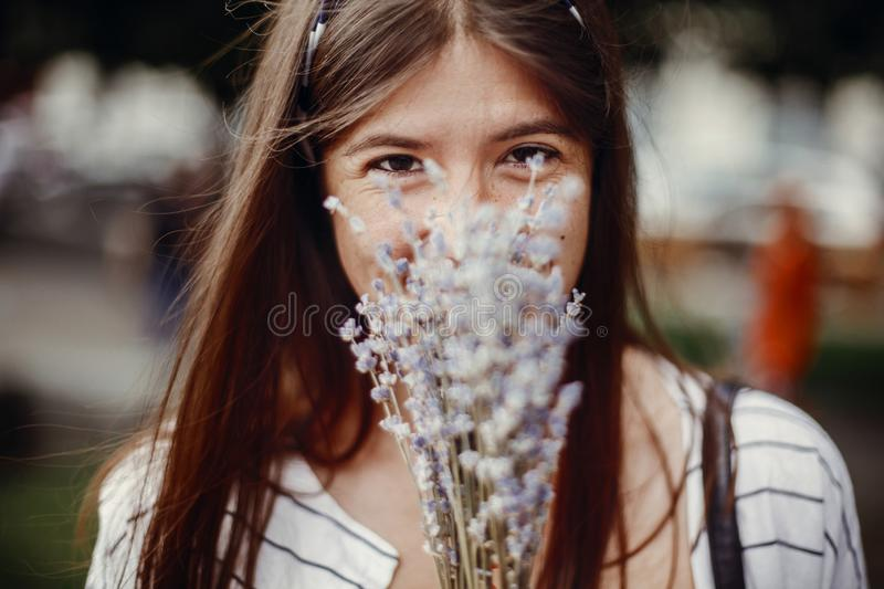Happy hipster girl enjoying aroma of lavender bouquet. Calm atmospheric moment. Beautiful stylish young woman holding amazing lav. Ender flowers and smelling royalty free stock images