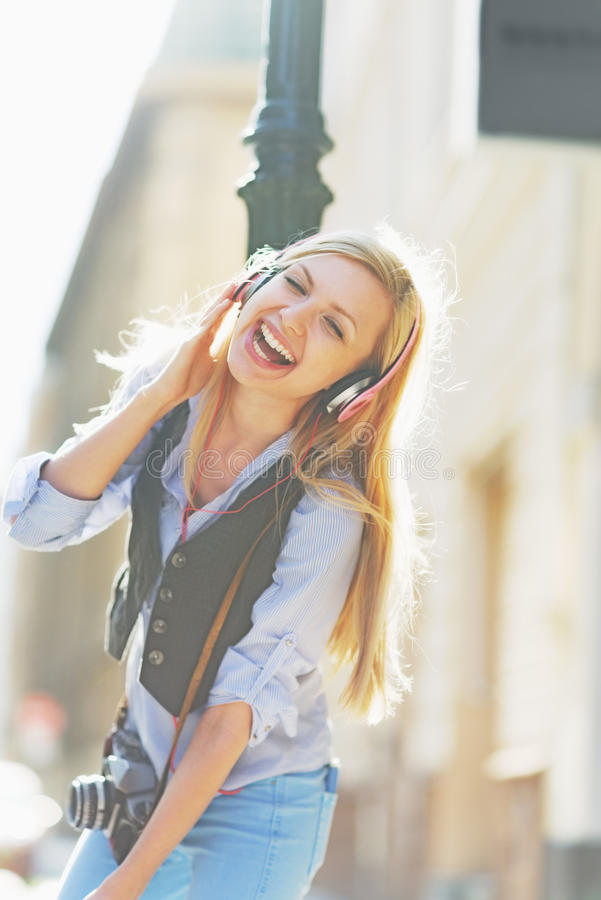 Happy hipster girl listening music on city street and dancing. Happy hipster blonde girl listening music on city street and dancing royalty free stock photos
