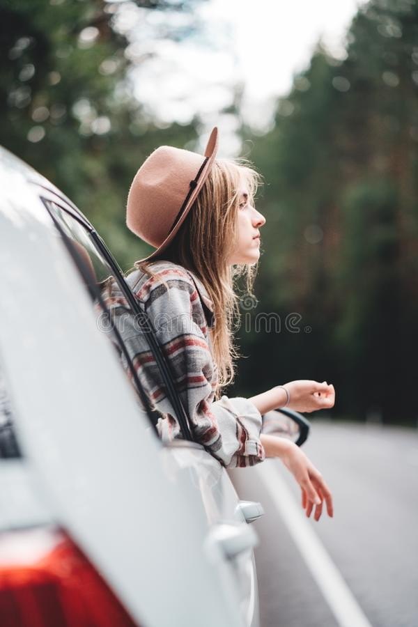 Happy hipster girl traveling adventure vacations. Boho woman sitting in car looking from window on view in country road stock photography