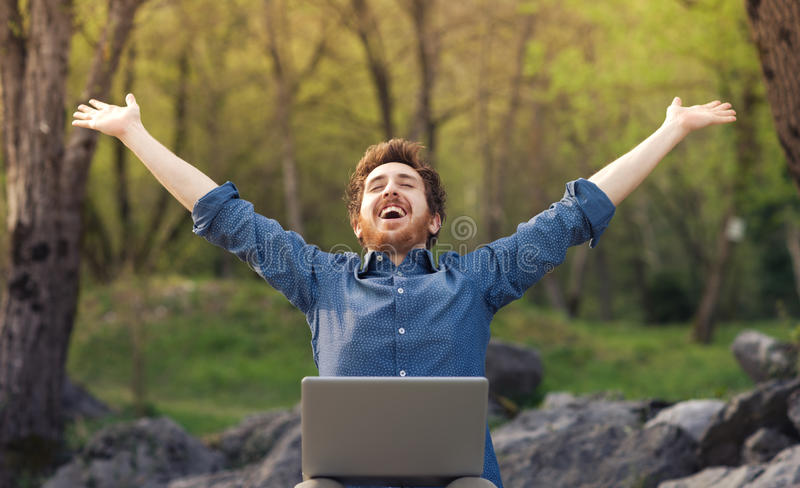 Happy hipster with laptop in the forest stock images